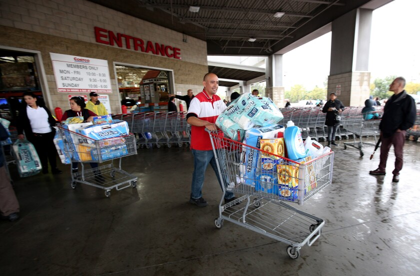 A shopper is among the first to exit Costco in Burbank after hundreds of customers lined up before doors opened, most looking for water, toilet paper, paper towels and cleaning supplies on Friday. Water and other necessities were out of stock within 20 minutes after the store opened.