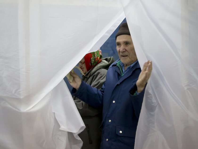 An elderly man exits a voting cabin after casting a vote in the Crimean referendum in Simferopol, Ukraine, Sunday, March 16, 2014. Residents of Ukraine's Crimea region are voting in a contentious referendum on whether to split off and seek annexation by Russia. (AP Photo/Vadim Ghirda)