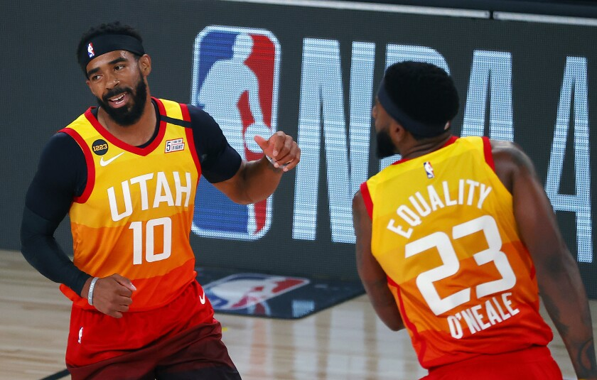 Utah Jazz' Mike Conley (10) celebrates a three-point basket with teammate Royce O'Neale (23) against the Denver Nuggets during the first quarter of an NBA basketball game Saturday, Aug. 8, 2020, in Lake Buena Vista, Fla. (Kevin C. Cox/Pool Photo via AP)