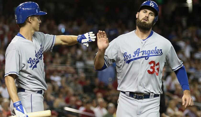 Dodgers pitcher Zack Greinke congratulates left fielder Scott Van Slyke (33) after he scored in the fourth inning against the Diamondbacks on Friday night in Phoenix.