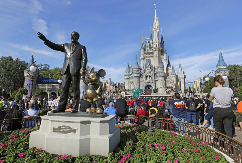 FILE - In this Jan. 9, 2019 photo, guests watch a show near a statue of Walt Disney and Micky Mouse in front of the Cinderella Castle at the Magic Kingdom at Walt Disney World in Lake Buena Vista, part of the Orlando area in Fla. Officials from SeaWorld and Disney World say they hope to open their theme parks in Orlando, Fla., in June and July. A city task force approved the plans on Wednesday, May 27, 2020. (AP Photo/John Raoux, File)