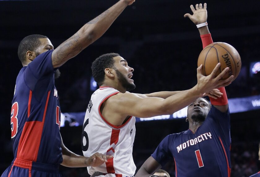 Toronto Raptors guard Cory Joseph, center, makes a layup defended by Detroit Pistons forward Marcus Morris, left, and guard Reggie Jackson (1) during the first half of an NBA basketball game, Sunday, Feb. 28, 2016, in Auburn Hills, Mich. (AP Photo/Carlos Osorio)