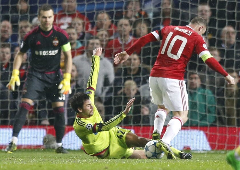 Manchester United's Wayne Rooney is tackled by CSKA's Georgy Shchennikov during the Champions League Group B soccer match between Manchester United and CSKA Moskva at Old Trafford Stadium, Manchester, England, Tuesday, Nov. 3, 2015. (AP Photo/Jon Super)
