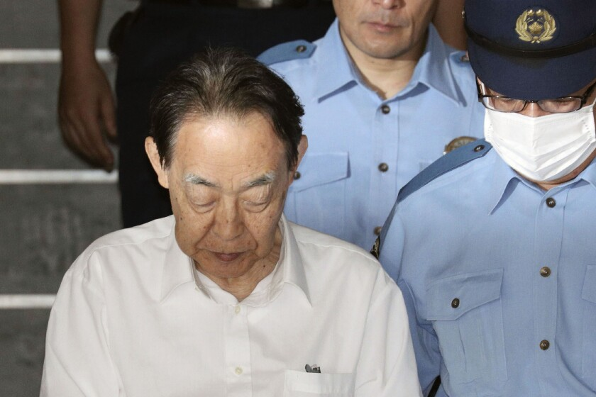 Hideaki Kumazawa, a former senior government official in Japan, is led out of a police station in Tokyo on June. 3.