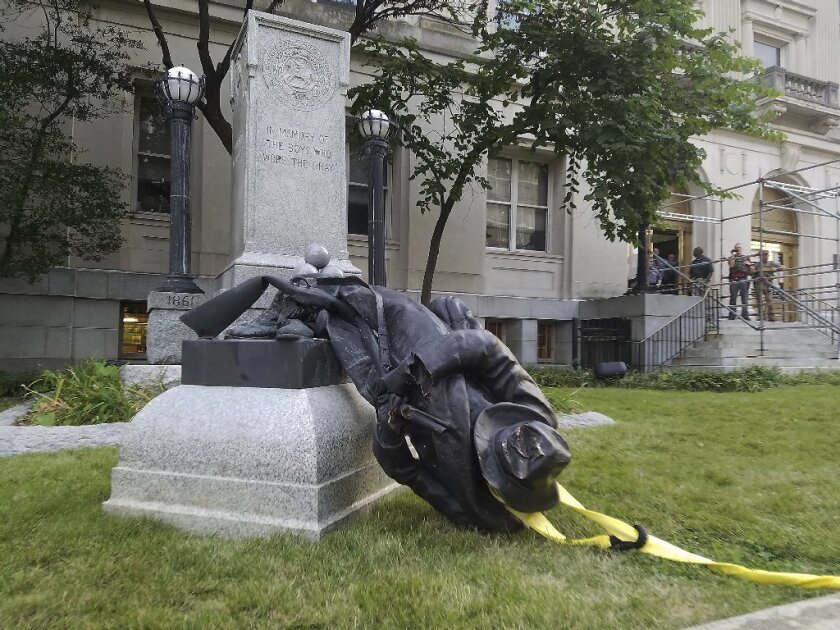 A toppled Confederate statue lies on the ground on Monday, Aug. 14, 2017, in Durham, N.C. Activists used a rope to pull down the monument outside a Durham courthouse. The Durham protest was in response to a white nationalist rally held in Charlottesville, Va, over the weekend.