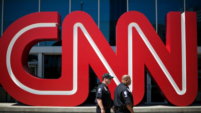 Security guards walk past the entrance to CNN headquarters in Atlanta. CNN is owned by Time Warner Inc., which is pursuing a sale to AT&T.