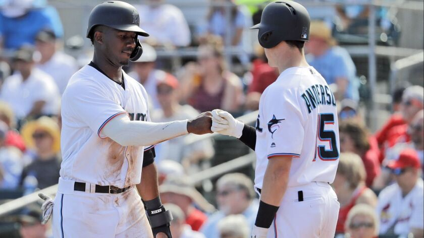 Miami Marlins' Lewis Brinson, left, is congratulated by teammate Brian Anderson after scoring during