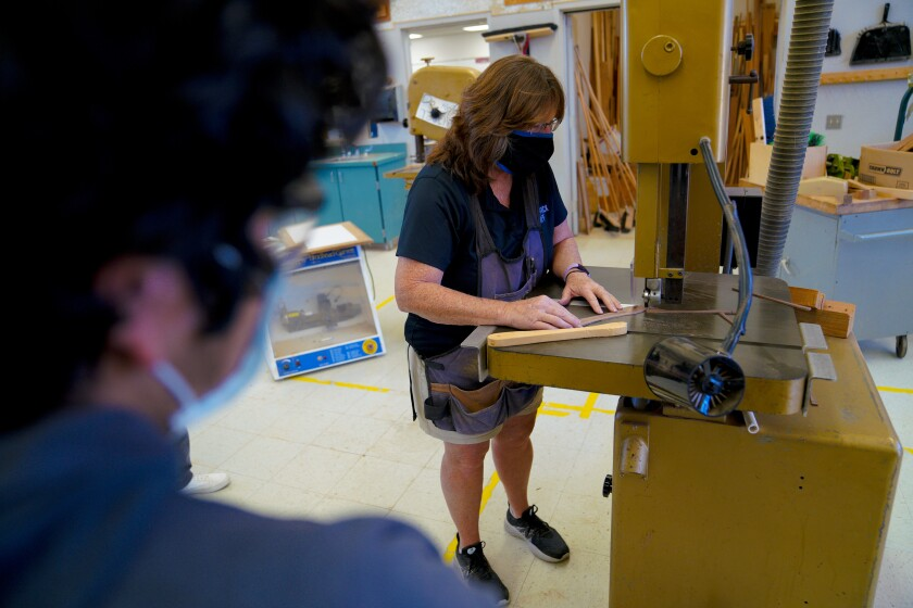Kathryn Worley demonstrated for his students on how to use the shop's band saw.