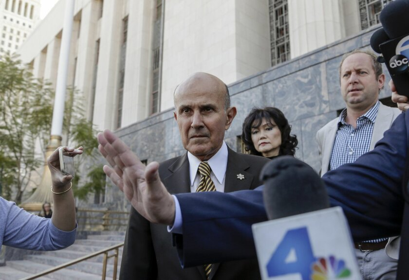 """Former Los Angeles Sheriff Lee Baca, left, and his wife, Carol leave U.S. Court House building in Los Angeles on Wednesday, Feb. 10, 2016. Baca signed a plea agreement that said he ordered deputies to intimidate an FBI agent and """"do everything but put handcuffs on her."""" Baca later lied to federal p"""