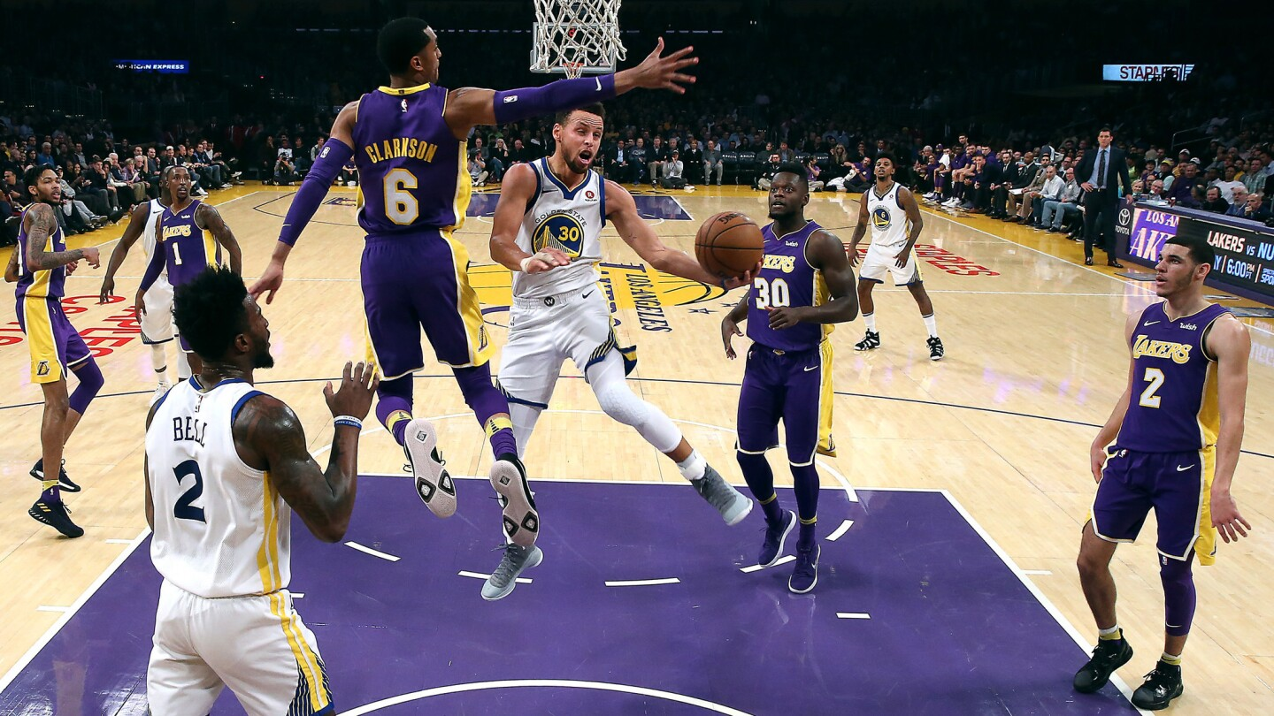 Warriors guard Stephen Curry drives past Lakers guard Jordan Clarkson for a first-half shot.