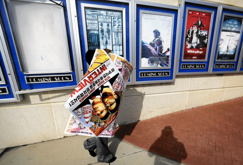 """A poster for """"The Interview"""" is carried away by a worker after being pulled from a display case Wednesday at a Carmike Cinemas movie theater in Atlanta."""