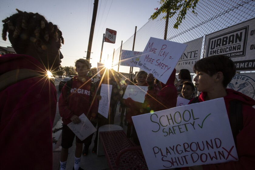 Parents and students gather to protest against a fence nearing completion at Long Beach's Fremont Elementary School, which will close off the campus playground area during non-school hours.