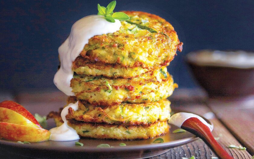 Caron's Zucchini Pancakes are made with grated zucchini and onions and mixed with eggs and panko, then sautéed in oil until they're brown and crispy.