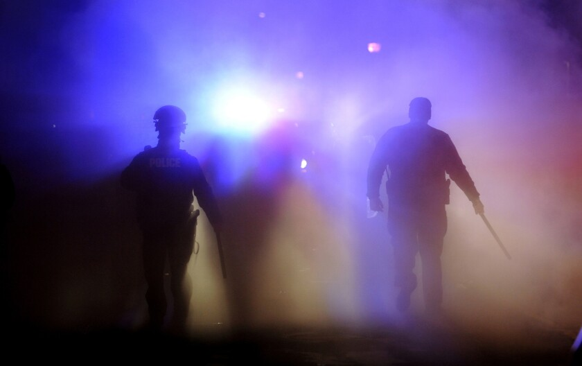 Officers walk through smoke from a burning police vehicle in front of Ferguson City Hall.