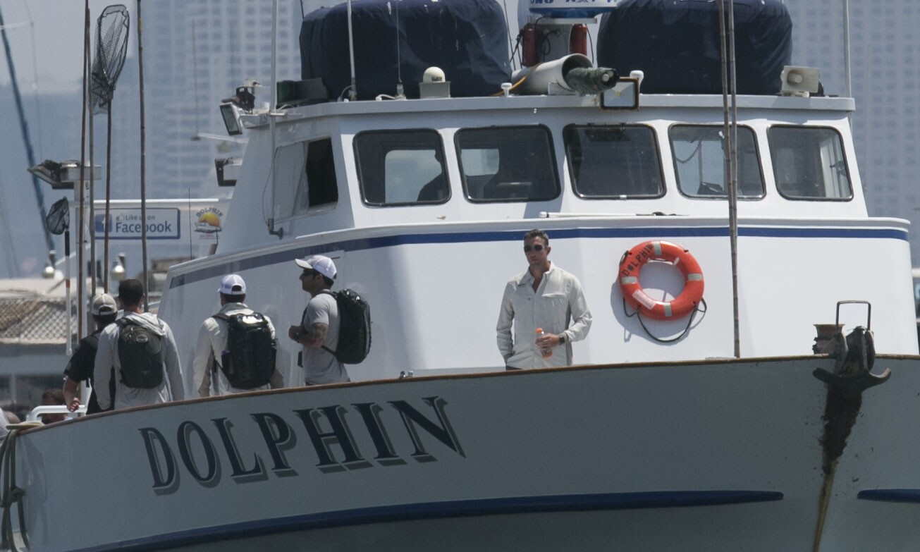 Duncan D. Hunter, right, on the bow of the fishing boat Dolphin as it came in to the landing.