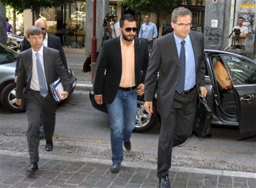 European Central Bank's (ECB) Klaus Masuch, right, and European Commission's director Matthias Mors, left, arrive for a meeting between Greece's new finance minister Yannis Stournaras and the debt inspectors from the European Central Bank, European Commission and International Monetary Fund, known