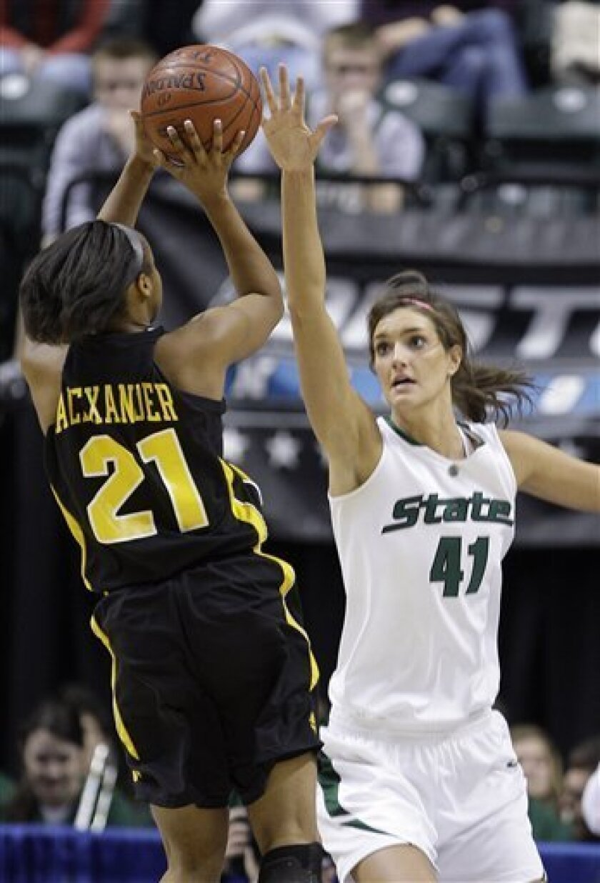 Iowa's Kachine Alexander, left, shoots over the outstretched hand of Michigan State's Allyssa DeHaan in the first half of an NCAA college basketball game in the semifinals of the women's Big Ten Conference tournament in Indianapolis, Saturday, March 6, 2010. (AP Photo/Michael Conroy)