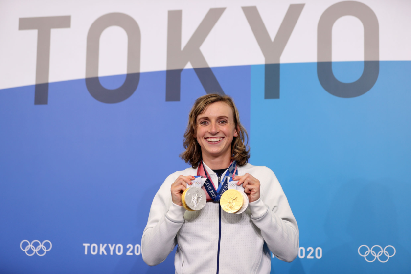 Katie Ledecky holds up her gold and silver medals at the Tokyo Olympics