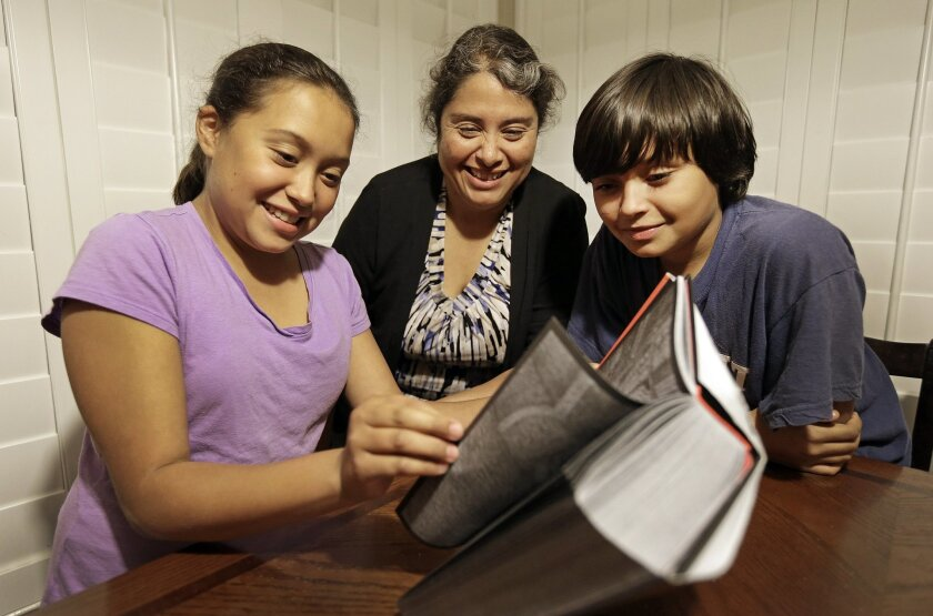 In this Nov. 10, 2014 photo, Rosaisela Rodriguez, center, reads with her children Isabel Gutierrez, left, and Rafael Gutierrez, at their home in Pleasant Hill, Calif. Rodriguez deliberately didn't declare that her twin son and daughter knew Spanish when she enrolled them in school, adding that most