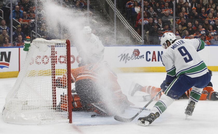 Vancouver Canucks' J.T. Miller (9) watches the puck go past Edmonton Oilers goalie Mike Smith (41) during the first period of an NHL hockey game, Saturday, Nov. 30, 2019, in Edmonton, Alberta. (Jason Franson/The Canadian Press via AP)