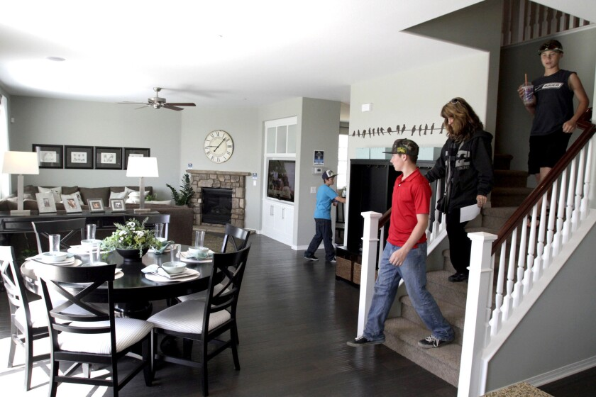 Rates for 30-year mortgages are at a 10-week low, Freddie Mac says. Above, a family tours a model home in San Bernardino.