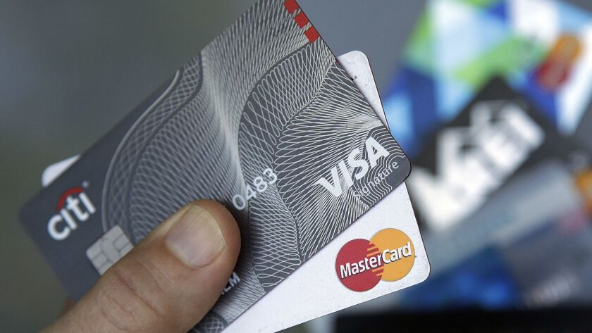 FILE- In this June 15, 2017, file photo, credit cards are displayed in Haverhill, Mass. Visa and Mas