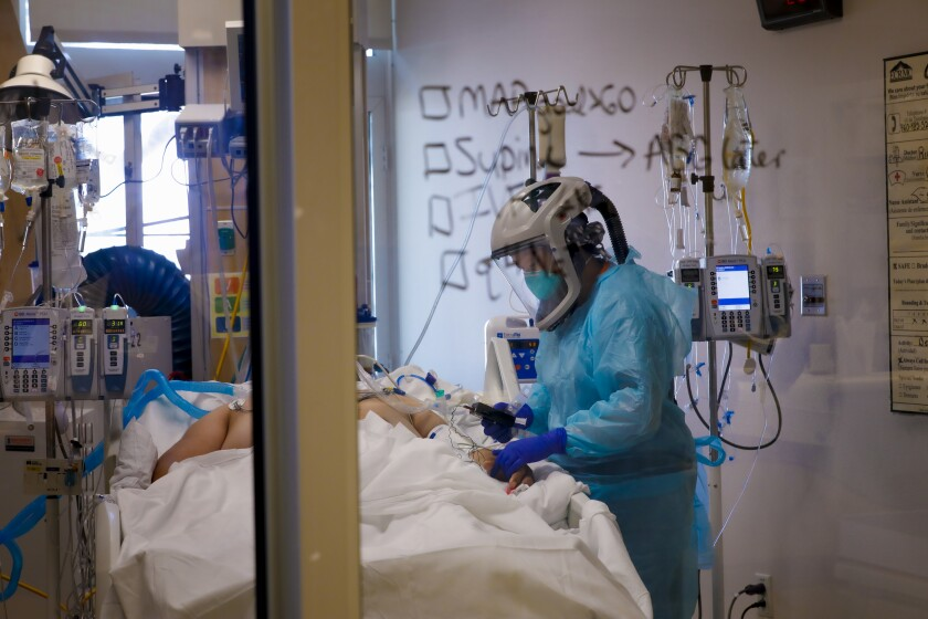 Wearing a PAPR PPE, Kristen Wilson, RN checks on a COVID-19 patient.