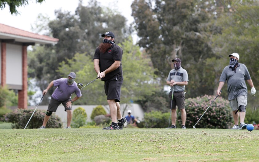 Golfer Eddie Rodriguez, 30, tees off as he begins a round of golf with, from left to right, Nick Pederson, 29, brother Justin Rodriguez, 29, and Todd Carbello, 58, at Costa Mesa Country Club on Wednesday.