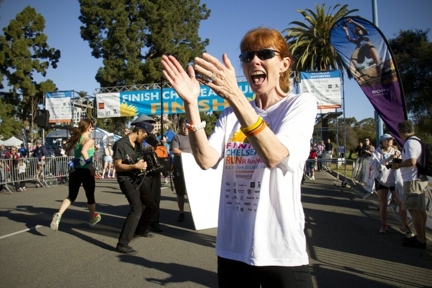 Kelly King gets excited as runners near the finish line in the third annual Finish Chelsea's Run in honor of her daughter, Chelsea King, at Balboa Park.