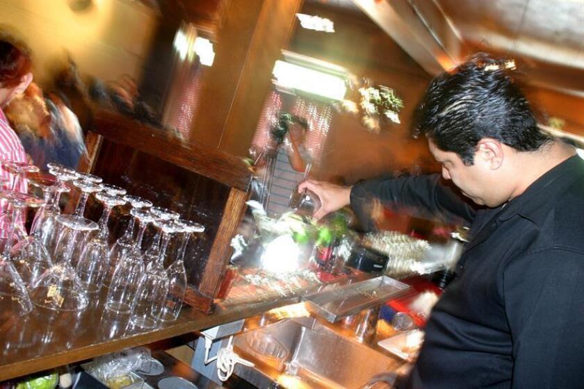 Un cantinero prepara bebidas durante una cena de Navidad. EFE/Archivo