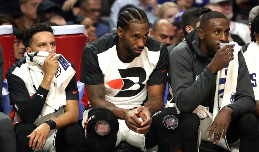 Clippers star Kawhi Leonard, center, sits on the bench during the first half against the Portland Trail Blazers.