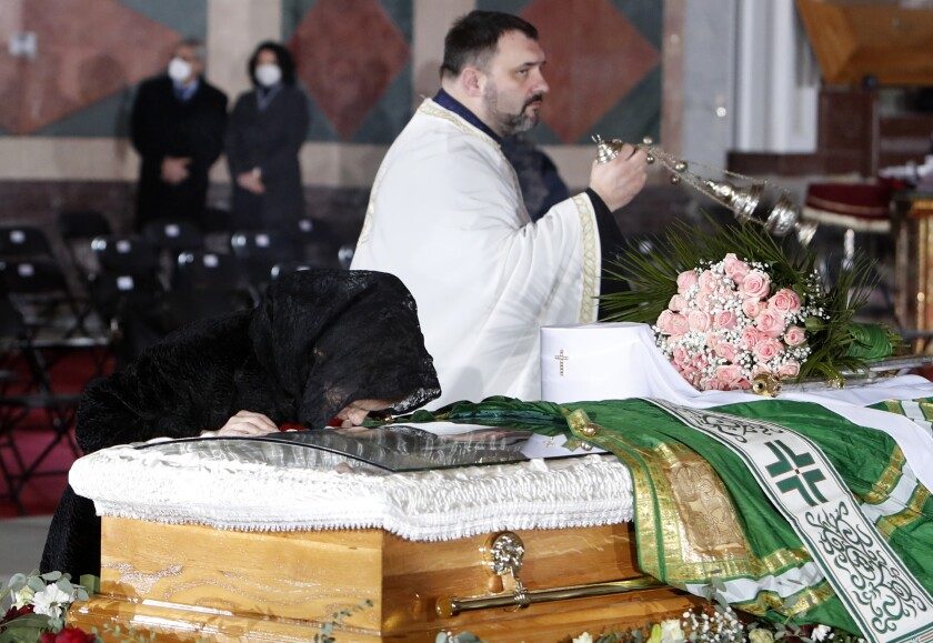 A woman kisses the coffin of Patriarch Irinej during the funeral procession at the St. Sava Temple in Belgrade, Serbia, Sunday, Nov. 22, 2020. The 90-year-old Irinej died early on Friday, nearly three weeks after he led the prayers at a funeral of another senior church cleric in neighboring Montenegro, who also died after testing positive for the virus. (AP Photo/Darko Vojinovic)