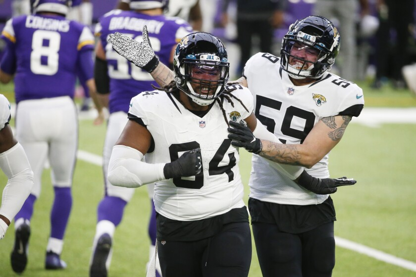 Jacksonville Jaguars defensive end Dawuane Smoot (94) celebrates with teammate Aaron Lynch (59) after a sack during the first half of an NFL football game against the Minnesota Vikings, Sunday, Dec. 6, 2020, in Minneapolis. (AP Photo/Bruce Kluckhohn)