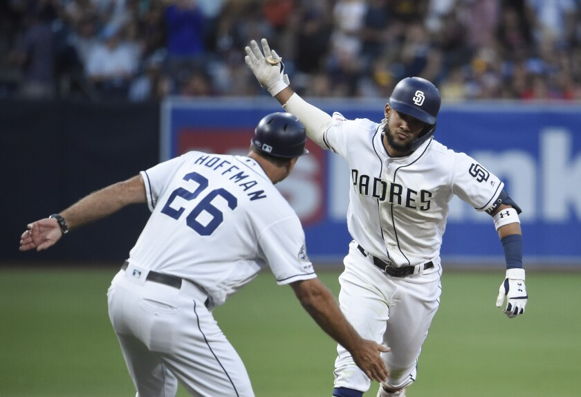Fernando Tatis Jr. is congratulated by Padres third base coach Glenn Hoffman after hitting home run to lead off the bottom of the first inning Thursday night.