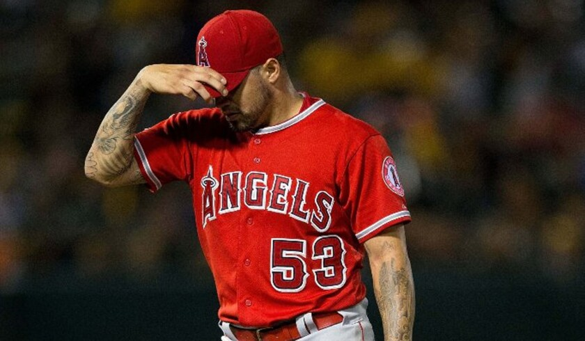 Angels starting pitcher Hector Santiago returns to the dugout after being relieved in the third inning against the Athletics on Monday.