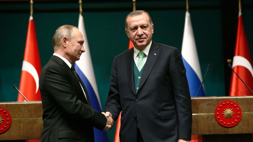 Turkey's President Recep Tayyip Erdogan, right, shakes hands with Russia's President Vladimir Putin following their joint news statement after their meeting at the Presidential Palace in Ankara, Turkey, on Dec. 11.