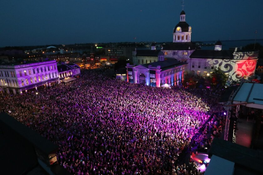"""People who could not get a ticket gather in Springer Market square to listen to the Tragically Hip in downtown Kingston, Ontario, Saturday, Aug. 20, 2016. The Tragically Hip mixed fan favorites, newer songs and some politics on Saturday night during the final show of their """"Man Machine Poem"""" tour."""