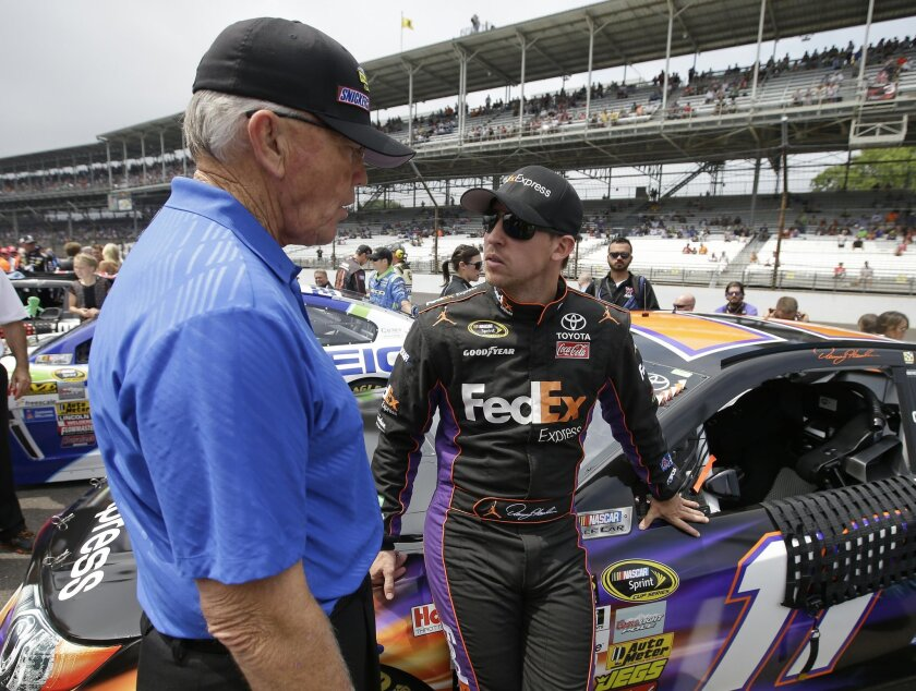 NASCAR team owner Joe Gibbs, left, talks with Denny Hamlin before the Brickyard 400 auto race at Indianapolis Motor Speedway in Indianapolis, Sunday, July 27, 2014. (AP Photo/Darron Cummings)