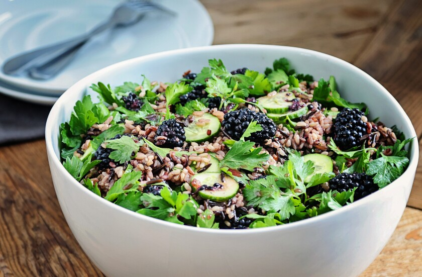 A white bowl holds a wild rice and herb salad with a fish sauce vinagrette.