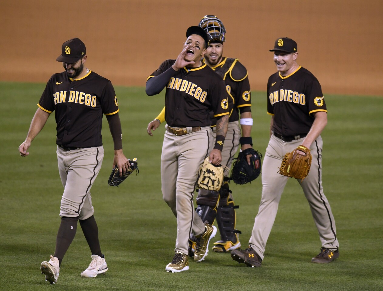 LOS ANGELES, CALIFORNIA - APRIL 25: (L-R) Eric Hosmer #30, Manny Machado #13, Victor Caratini #8 and Mark Melancon #33 of the San Diego Padres celebrate an 8-7 win over the Los Angeles Dodgers in eleventh innings at Dodger Stadium on April 25, 2021 in Los Angeles, California. (Photo by Harry How/Getty Images)