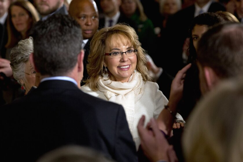 FILE - In this Jan. 5, 2016, file photo, people applaud former Arizona Rep. Gabby Giffords as she arrives in the East Room of the White House in Washington, to hear President Obama speak about steps his administration is taking to reduce gun violence. An official says a lawsuit filed in the name of the man who shot former U.S. Congresswoman Gabby Giffords is bogus. Cosme Lopez with the U.S. Attorney's Office District of Arizona says attorneys for convicted killer Jared Lee Loughner notified the court that Loughner didn't file or authorize the lawsuit. (AP Photo/Jacquelyn Martin, File)