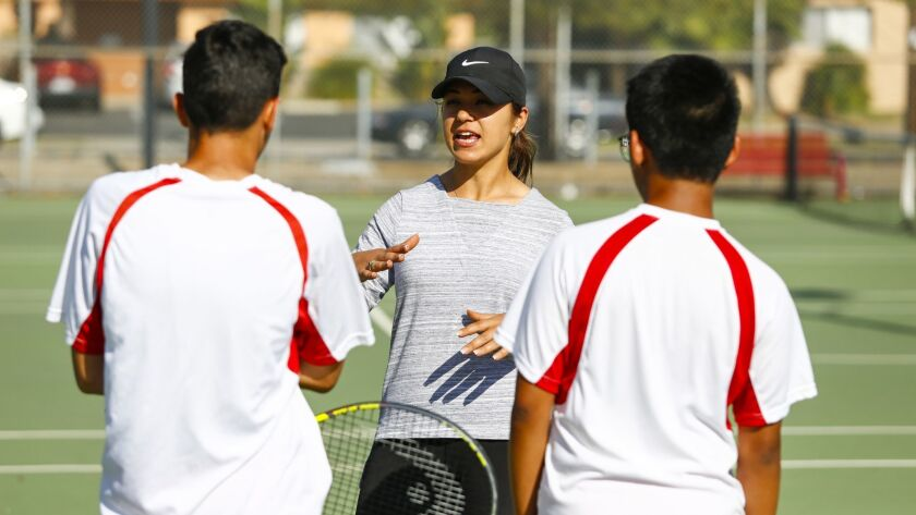 El Cajon Valley High School boys tennis coach Lidia Hormous talks with her doubles team, Ali Aljabarri and Miguel Lorenzo.