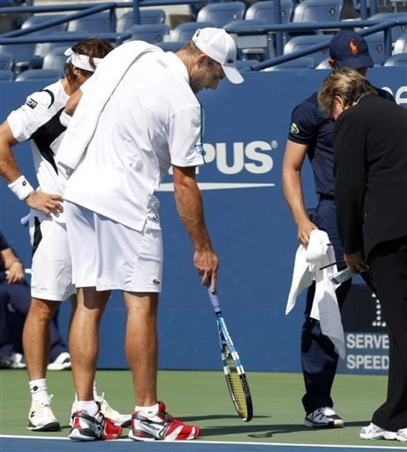 Andy Roddick of USA points to a wet spot on the court to an official as opponent David Ferrer of Spain, far left, looks on prior to their match on Louis Armstrong Stadium in the fourth round at the U.S. Open tennis tournament in New York, Thursday, Sept. 8, 2011. The court was deemed unplayable due to water coming up through the playing surface after two days of steady rain and delays.(AP Photo/Charles Krupa)