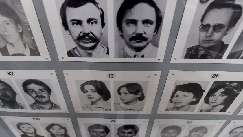 Passport photos used by border guards in East Berlin hang on the wall of the Wende.