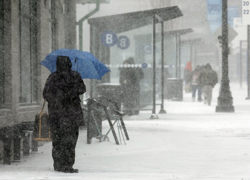 A passenger waits in the snow to board a bus at Kennedy Plaza in Providence, R.I., Monday, Feb. 8, 2016. Massachusetts, Rhode Island and eastern Connecticut, could see winter storm conditions with an accumulation of 4 to 8 inches. The heaviest snowfall is expected during Monday's morning commute th