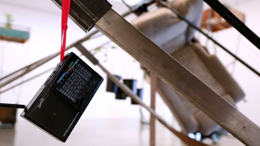 A transistor radio, tuned to a Los Angeles-area station, is suspended from one of Cruzvillegas's sculptures by a pair of women's underwear.