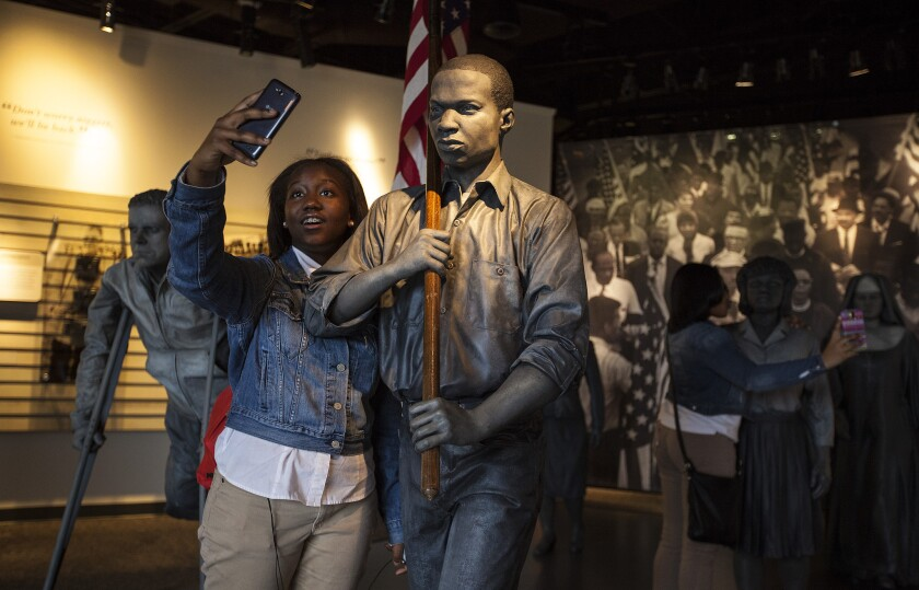 Imani Washington, 13, of Atlanta, takes a selfie with a bronze statue of civil rights marcher Timothy Mays at the Lowndes County Interpretive Center on the Selma to Montgomery National Historic Trail.