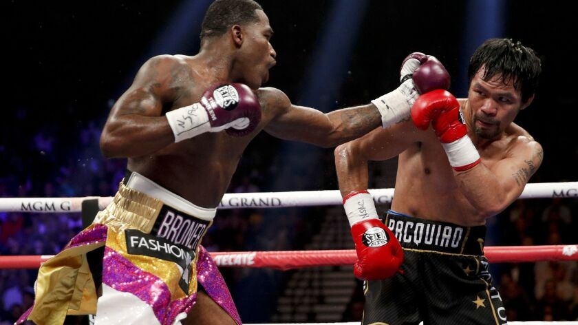 Manny Pacquiao, right, blocks a punch from Adrien Broner during WBA welterweight title boxing match