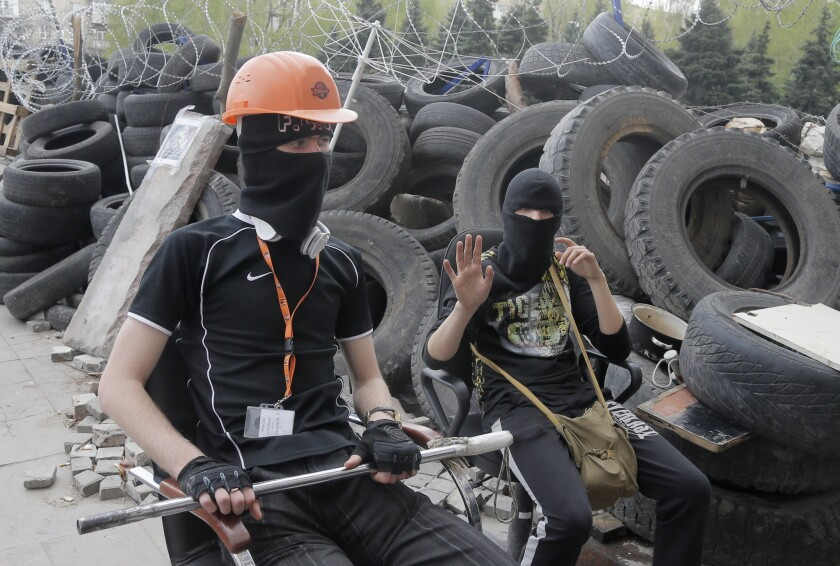Pro-Russia activists stand guard at a barricade at the regional administration building in Donetsk, Ukraine. Pro-Russia gunmen in eastern Ukraine admitted Wednesday that they are holding an American journalist who has not been seen since early Tuesday.