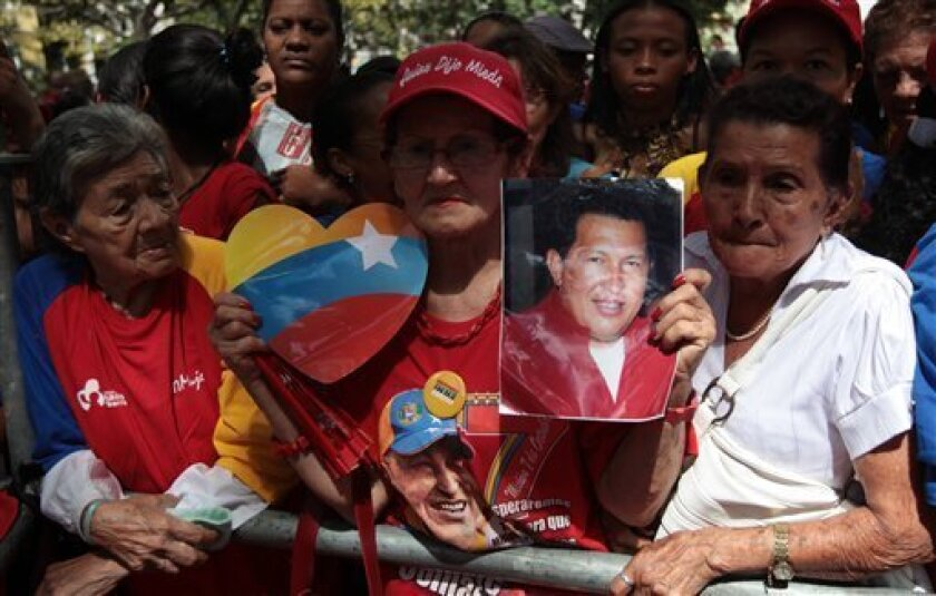 """A woman holds a picture of Venezuela's President Hugo Chavez as supporters gather at Simon Bolivar square in Caracas,Venezuela, Sunday Dec. 9, 2012. Chavez is to return to Cuba Sunday for another surgery in his battle against cancer, which has led him to speak publicly of a successor for the first time. Chavez said Saturday that if there are """"circumstances that prevent me from exercising the presidency further"""" Vice-President Nicolas Maduro should replace him for the remainder of his term.(AP Photo/Fernando Llano)"""
